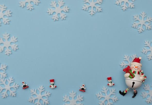 Sfondo natale blu con decorazioni natalizie e fiocchi di neve bianchi