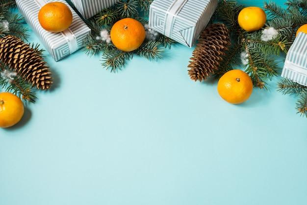 Sfondo di natale blu con albero di abete e mandarini.