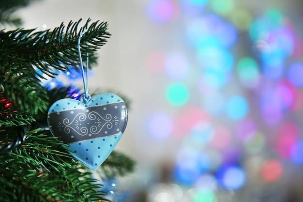 Cuore blu di natale su un abete su sfondo sfocato, primo piano