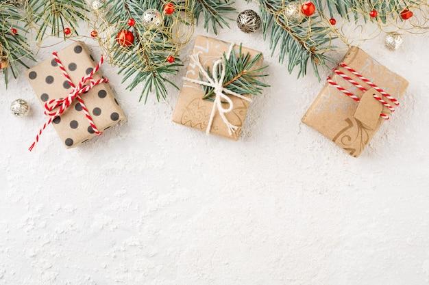 Bordo di natale dei contenitori di regalo di natale, ornamenti, abete rosso su priorità bassa bianca.