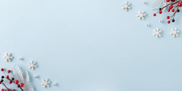 Bordo di natale fatto di fiocchi di neve e bacche rosse su sfondo blu. concetto di inverno. lay piatto.