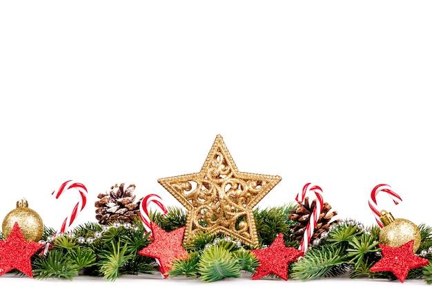 Bordo di natale con rami di albero con palline dorate, caramelle e grande stella