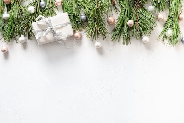 Bordo di natale con regalo bianco, pastello rosa e palline d'argento, rami sempreverdi su bianco. vista dall'alto. lay piatto