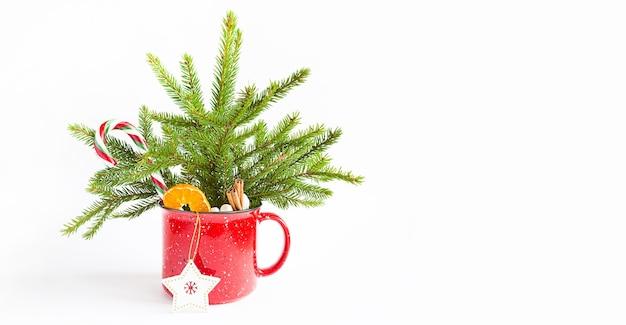 Mazzo di natale in una tazza rossa fatta di abete rosso vivo e decorazioni e accessori festivi, giocattoli per l'albero di natale, dolci. anno nuovo, atmosfera festosa, floristica su sfondo bianco con spazio per le copie