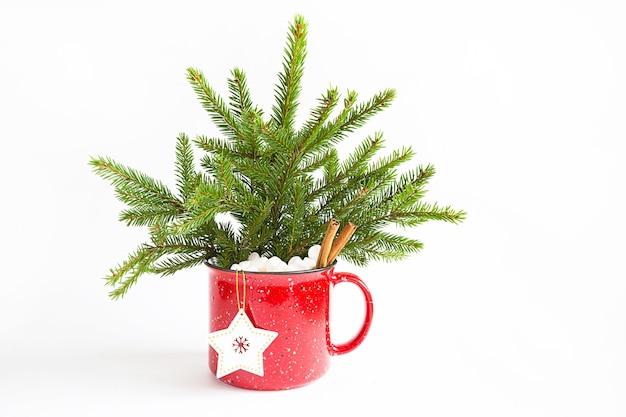 Mazzo di natale in una tazza rossa fatta di abete rosso vivo e decorazioni e accessori festivi, giocattoli per l'albero di natale, dolci. anno nuovo, atmosfera festosa, floristica su sfondo bianco