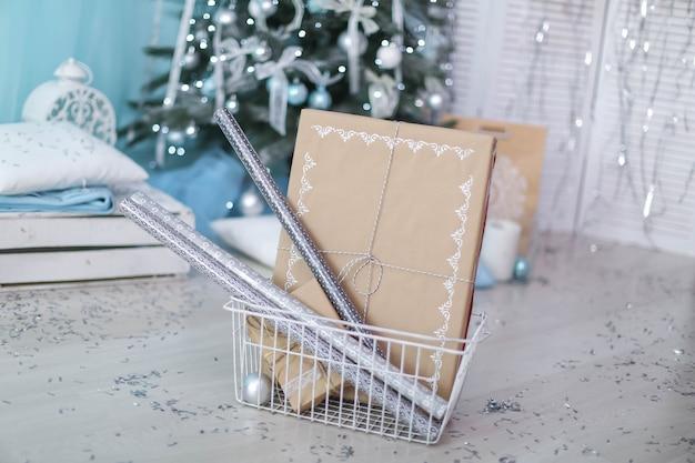 Scatola di natale con un regalo legato con un nastro sullo sfondo di un albero di natale.
