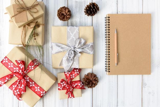 Scatole regalo di natale marrone impostato avvolto con nastro rosso e taccuino di carta su fondo di legno bianco, piatto laici