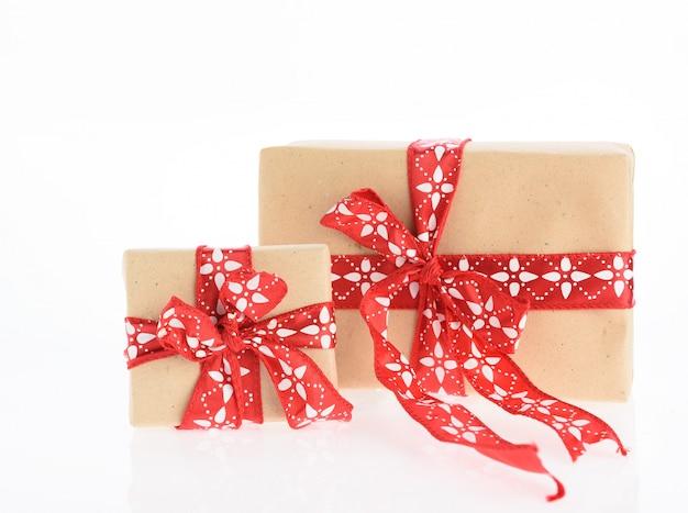 Scatole regalo di natale marrone avvolto con nastro rosso isolato su sfondo bianco