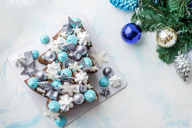 Torta di natale a forma di albero di natale. torta di natale con sfere di cioccolato e fiocchi di neve. cioccolato con decorazione blu.