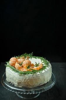 Torta di natale con mandarini, mandorle e rosmarino su un supporto. torta natalizia con panna montata. tavolo scuro. spazio per il testo.