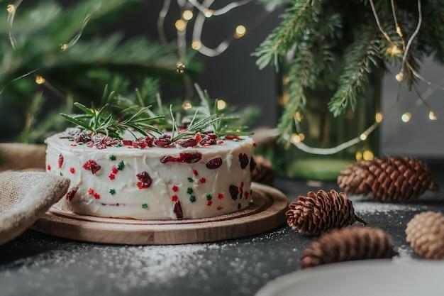 Torta di natale con crema di formaggio bianco, decorata con mirtilli rossi e rosmarino.