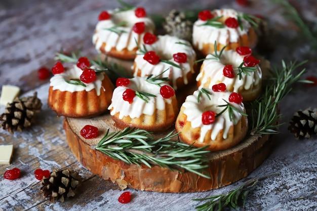 Dolci natalizi con glassa bianca, bacche rosse e rosmarino. decorazione natalizia. messa a fuoco selettiva.