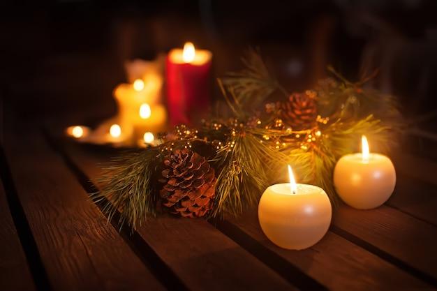 Candele di natale e ornamenti sul tavolo scuro con luci