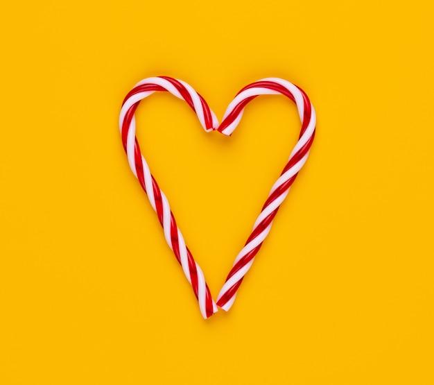 Canna di caramella di natale isolata su colore giallo