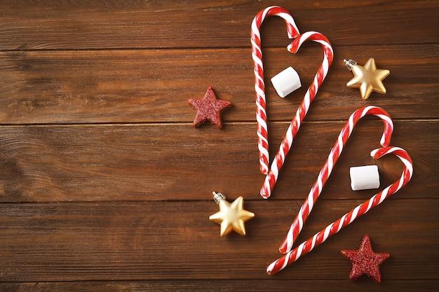 Bastoncini di zucchero e decorazioni natalizie su fondo in legno