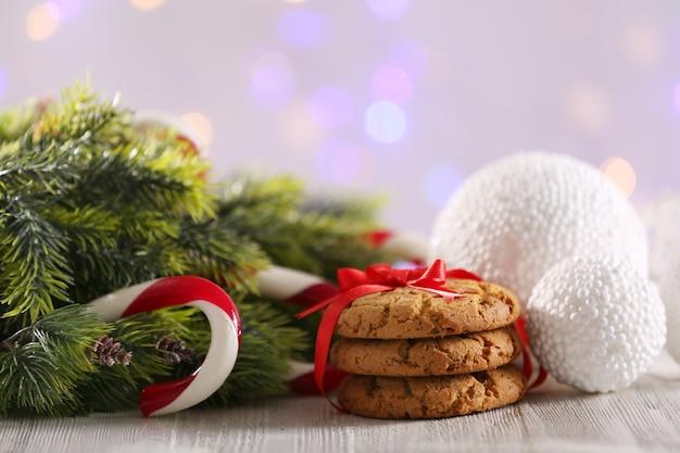 Bastoncini di zucchero di natale con decorazioni natalizie sul tavolo su sfondo chiaro