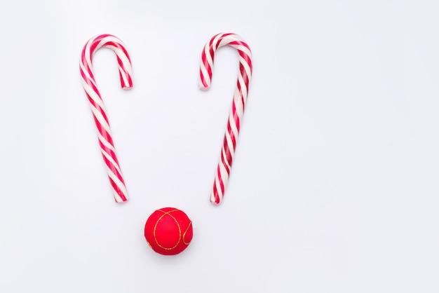 Caramelle di natale e palla rossa come cervi su sfondo bianco, copia dello spazio