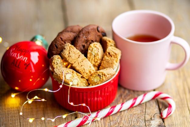 Caramelle di natale con un giocattolo sull'albero bevanda calda con biscotti al cioccolato fuoco del bengala in una tazza