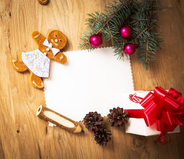 Cartolina di natale: regalo rurale in bianco, vintage e ramo di albero di natale su fondo in legno con regalo