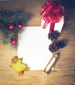 Cartolina di natale: regalo rurale in bianco, vintage e ramo di albero di natale su legno con regalo