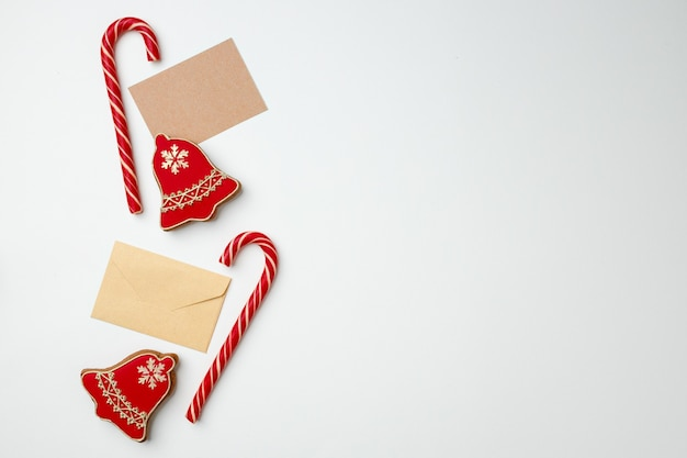 Cartolina di natale e bastoncini di zucchero sulla vista superiore del fondo bianco