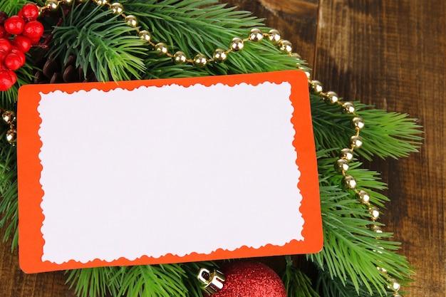 Cartolina di natale su ramo di abete su fondo in legno