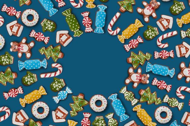 Cartolina di natale dal telaio dei biscotti allo zenzero su sfondo blu