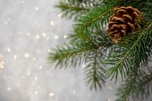 Cono del pino della cartolina di natale su un albero su una priorità bassa del bokeh
