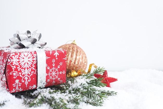 Biglietto natalizio. confezione regalo rossa con fiocco argento su rami di abete con neve, stelle e una palla di natale. copia spazio.