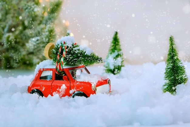 Biglietto natalizio. giocattolo auto d'epoca rossa che trasporta un albero di natale a casa attraverso un paese delle meraviglie invernale innevato. messa a fuoco selettiva.
