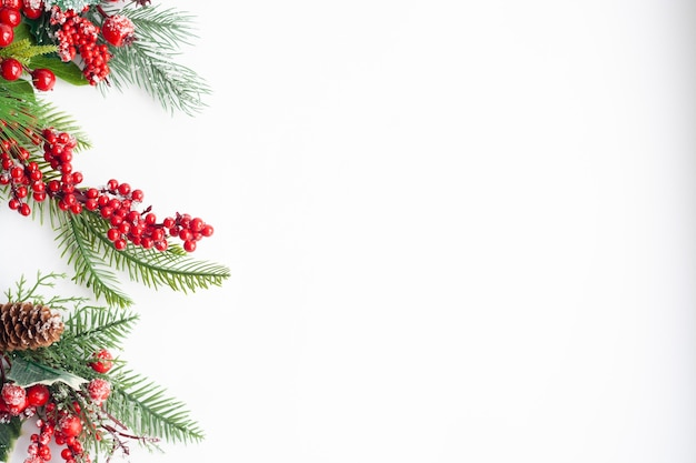Cartolina di natale, ramoscelli di abete rosso, bacche rosse e coni, cosparsi di neve, copia dello spazio
