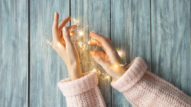 Cartolina di natale con bellissime luci di natale scintillanti con nido nelle mani su uno sfondo di legno