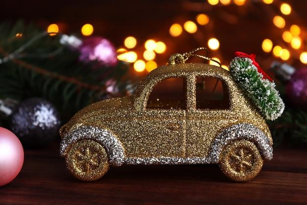 Cartolina di natale con decorazioni natalizie auto giocattolo luci rami di albero di natale e bokeh
