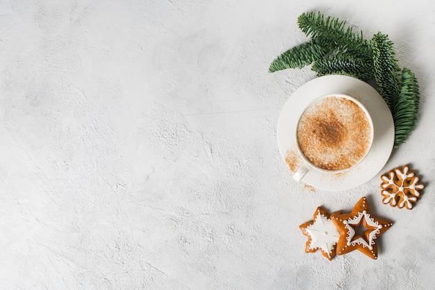 Cartolina di natale con una tazza di caffè, pino, abete e pan di zenzero su sfondo bianco, copia spazio, vista dall'alto