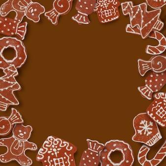 Cartolina di natale con cornice fatta di biscotti allo zenzero su uno sfondo marrone