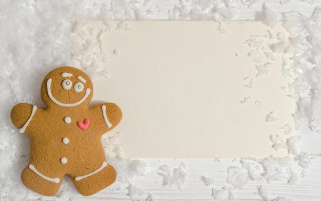 Cartolina di natale con l'omino di pan di zenzero con i fiocchi di neve. lay piatto