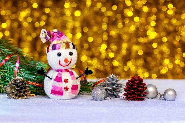 Cartolina di natale con pupazzo di neve e decorazioni natalizie su fondo oro con bokeh