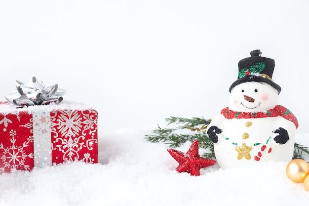Cartolina di natale con pupazzo di neve, confezione regalo rossa, rami di abete e stella nella neve. copia spazio.