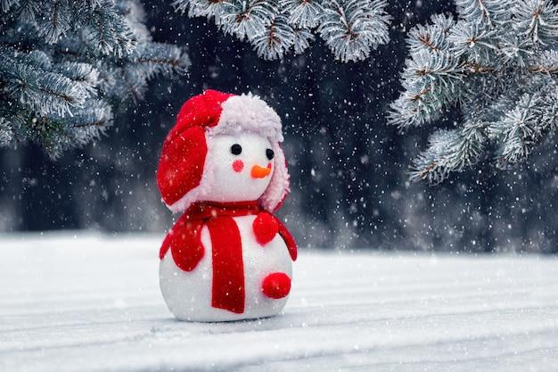 Cartolina di natale con un pupazzo di neve giocattolo nei boschi vicino all'abete rosso durante una nevicata. auguri di capodanno