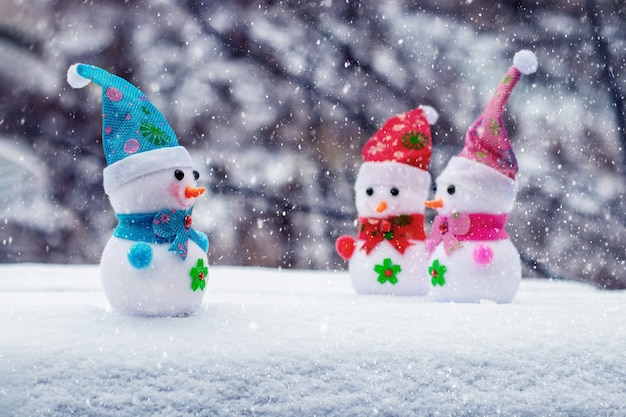 Cartolina di natale con pupazzi di neve giocattolo nella foresta durante una nevicata. auguri di capodanno