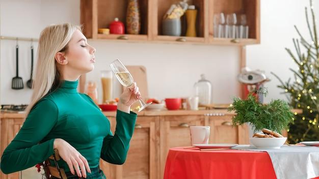 Celebrazione di natale. vista laterale della signora bionda che beve champagne al tavolo festivo in cucina.