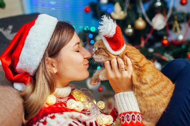 Celebrazione di natale con gatto donna che gioca e bacia un animale domestico con un cappello da babbo natale vicino all'albero di capodanno a casa