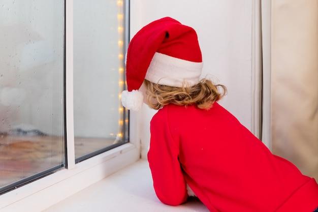 Elfo bambino di natale con cappello da babbo natale, elfo. buon natale e buone feste. bambina seduta vicino alla finestra e guardando la foresta invernale.