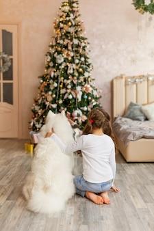 Natale ragazza del bambino con il cane samoiedo davanti a un albero di natale