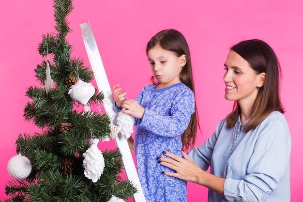 Concetto di natale, infanzia e persone - ragazza bambino in piedi sulla scala a pioli che decora l'albero