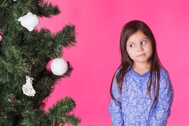 Concetto di natale, infanzia e persone - bambina guarda l'albero di natale sopra il rosa