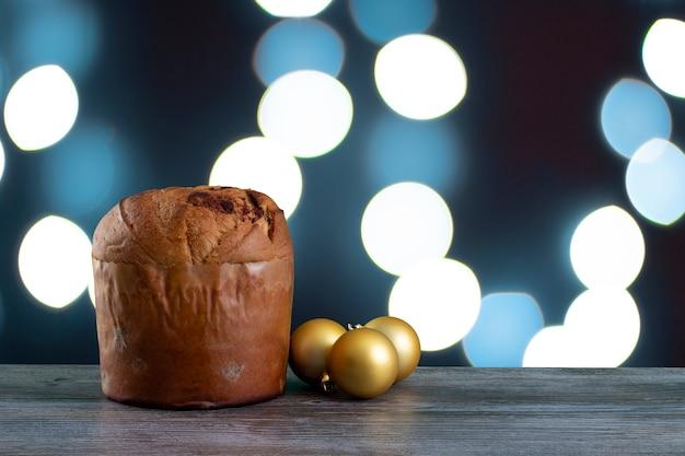 Panettone di torta al cioccolato natalizia con uno sfondo a luce blu o panettone chocotone