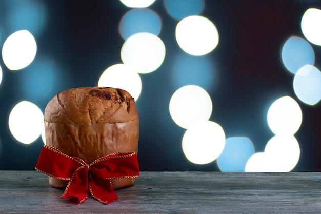 Panettone di torta al cioccolato di natale con un nastro rosso in uno sfondo di luce blu, panetone c