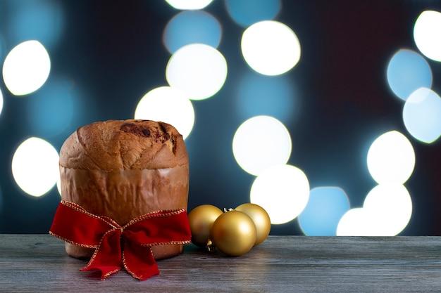 Panettone di torta al cioccolato di natale con un nastro rosso in uno sfondo di luce blu, panetone