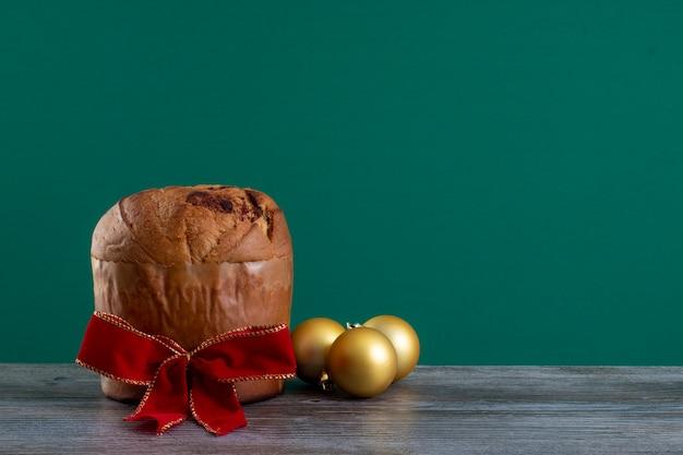 Panettone di torta al cioccolato natalizia con un nastro rosso in un panetone chroma backgroundor cho